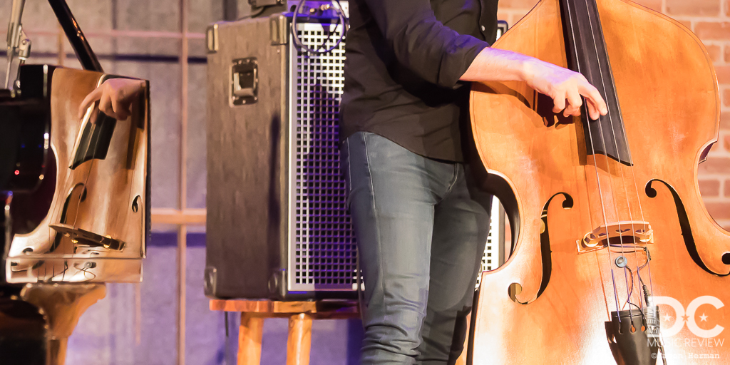 A portrait of Reid Anderson and his bass as reflected off of  Orrin Evans's piano.