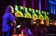 John K plays to a capacity audience and light show illuminated walls.