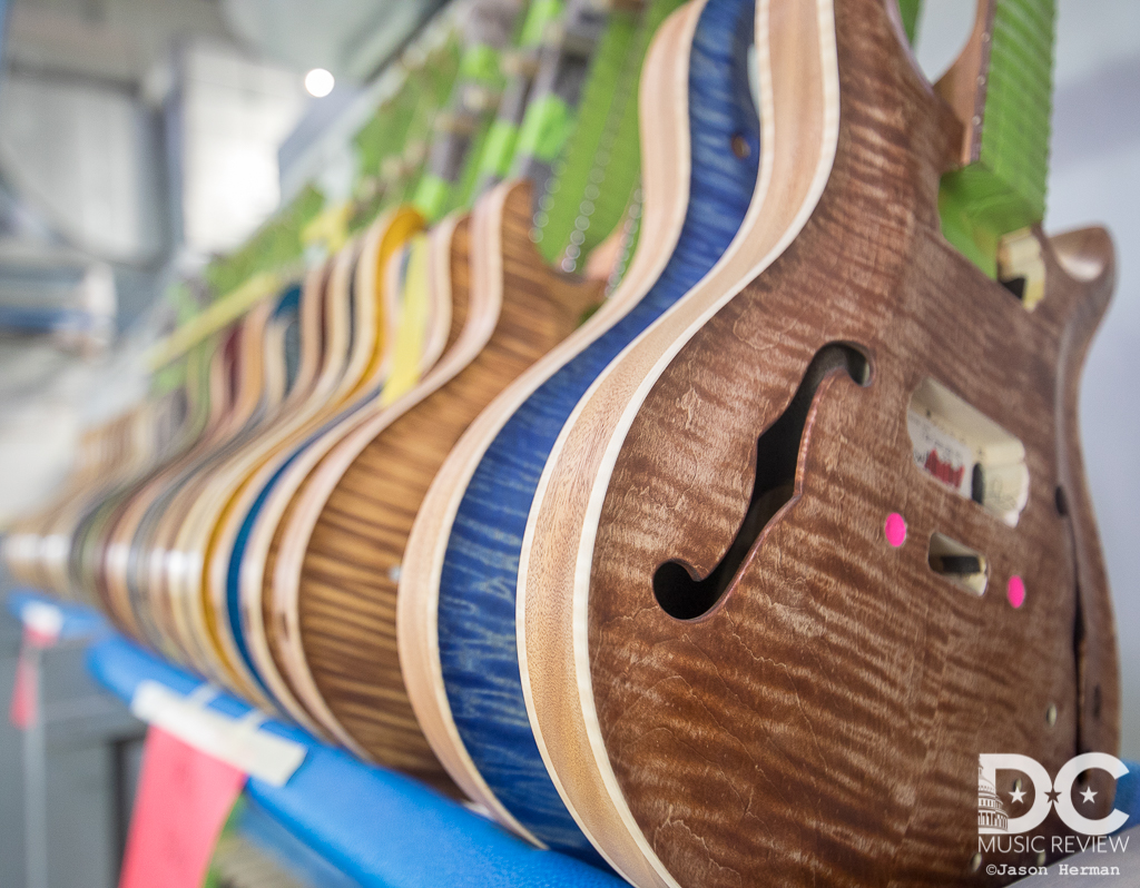 A row of hollow body guitars await their journey to becoming finished guitars.