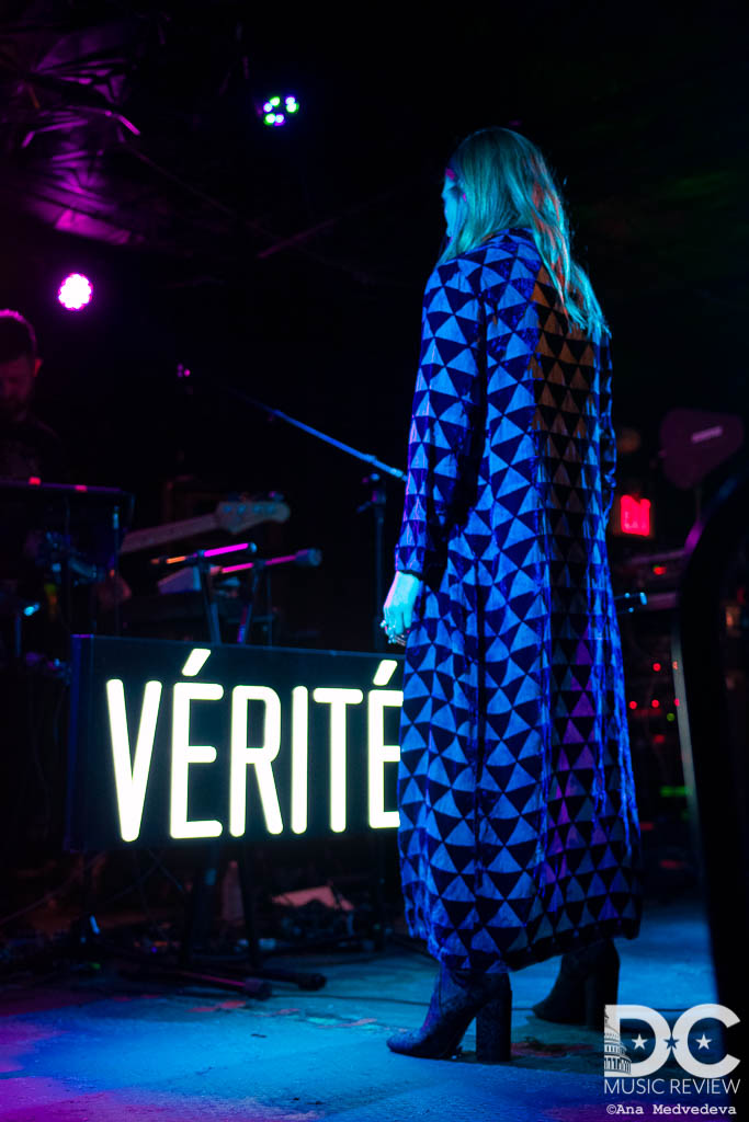 VÉRITÉ standing with her back to the audience