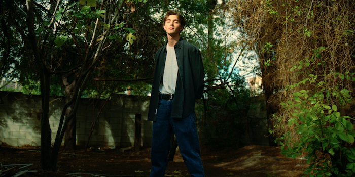 Greyson Chance dresed in blue jeans and dark green button down standing in a shady area with trees, holding his arms behind his back