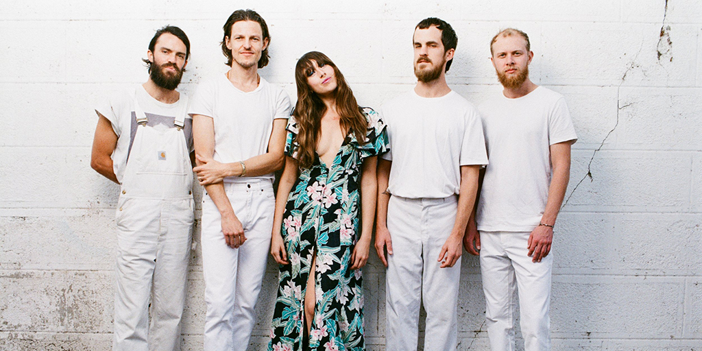 A photo of Amo Amo on a white background, with the lead singer in a bright dress surrounded by the other band members dressed in all white.